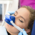 Photo of dental patient with mask on her face receiving nitrous oxide