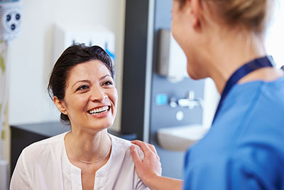 A woman smiling at her consulting physician.