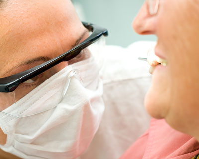 A doctor examining the dentures of an elderly patient