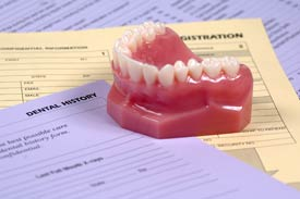 An upper mouth denture sitting on top of paper forms