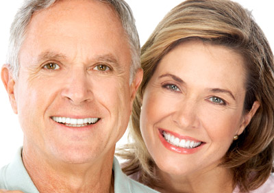 Middle-aged couple smiling with whitened teeth