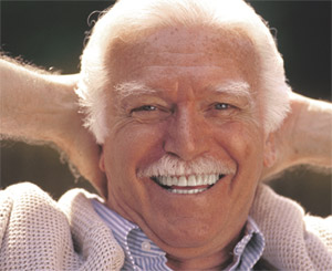 A smiling elderly man with dental implants